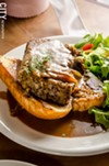The open-faced meatloaf sandwich, which has a rice-based filler and is studded with fresh mozzarella and beef, with caramelized onion gravy with parsley on top.