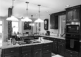 KURT BROWNELL - The remodeled kitchen - combines the modern and the old-fashioned: gleaming wood cabinets and an - original, weight-bearing beam.