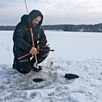 Ice Fishing Tim Thomas places a tip-up on the ice. A tip-up consists of a small wooden frame and flag that is triggered when a fish takes the bait on a corresponding hook and line. PHOTO BY KATHY LALUK