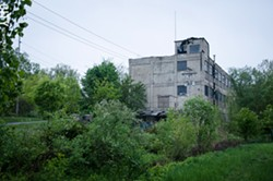 A vacant, dilapidated building at the end of Flint Street marks the Vacuum Oil site. - FILE PHOTO