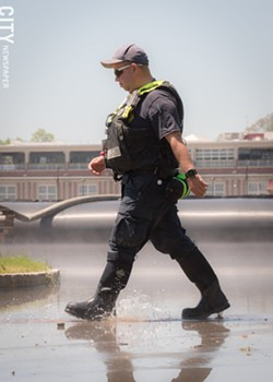 An emergency worker walks through flood waters. - PHOTO BY RYAN WILLIAMSON