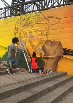 Youth apprentice Alex Baez Rivera looks on as artist Brittany Williams works on a section of the mural featuring Moses Rockwell. - PHOTO BY REBECCA RAFFERTY