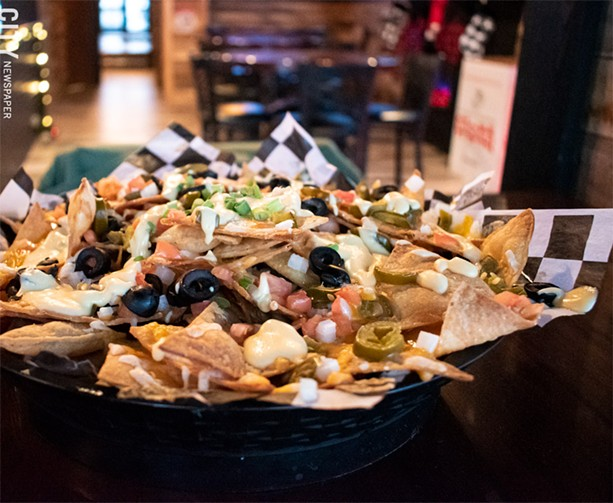 The loaded nachos were the best our writer has had in the city: tortillas buried in tomatoes, olives, cheddar jalapeños, spicy queso, and well-seasoned chicken. - PHOTO BY JACOB WALSH