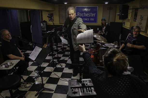 """Jeff Riales (standing) shares his version of """"No One Will Ever Know"""" with the house band for this year's """"If all Rochester Wrote the Same song"""" concert. - PHOTO BY MAX SCHULTE"""