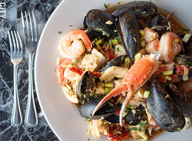 The Poseidon includes shrimp, scallops, lobster, crab, calamari, and mussels sautéed with sun dried tomatoes, roasted red peppers, and artichoke hearts in a lemon garlic sauce, over a bed of spinach rice. - PHOTO BY JACOB WALSH