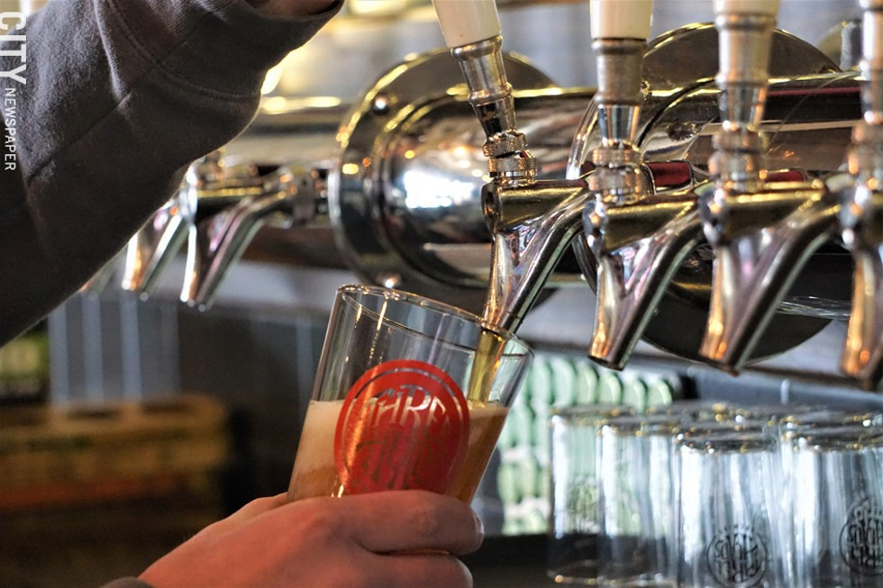 Three Heads' David Coniglio pouring a fresh glass of the brewery's Lancer Lager. - PHOTO BY GINO FANELLI