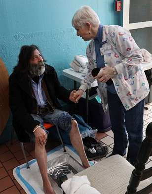 Debbie Sigrist, founder of the St. Joseph's House of Hospitality foot clinic, greets a guest. - PHOTO BY MAX SCHULTE