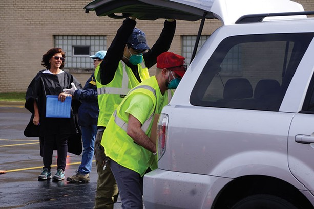 Foodlink volunteers load a 50-pound box of food into a vehicle during an emergency food distribution at Irondequoit Town Hall last week. - PHOTO BY GINO FANELLI