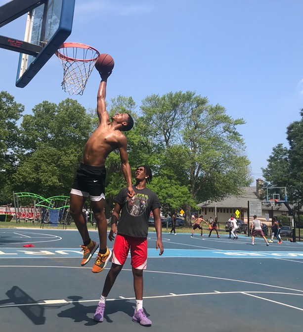 """Maurice """"Mo"""" McKinney, 16, reaches for a dunk with an assist from his brother, Christian Harmon, 15, at Cobb's Hill Park. - PHOTO BY DAVID ANDREATTA"""