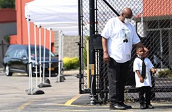 David Gantt's brother, Freddie Gantt hugs his grandson Dwight Abraham, while standing outside the Church of Love Faith Center where friends and family paid respects to the late lawmaker. - PHOTO BY MAX SCHULTE