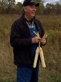 G. Peter Jemison, site manager at Ganondagan, braids together three ears of husked Iroquois White Corn. - PHOTO PROVIDED