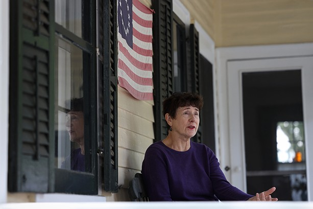 Lynn Barber on the porch of her historic home in Fairport. - PHOTO BY MAX SCHULTE