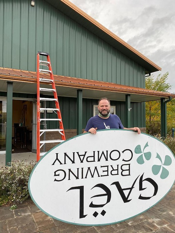 Big aLICe co-owner Kyle Hurst takes down the sign at the former GAEL Brewing Company in Geneva. - PROVIDED PHOTO