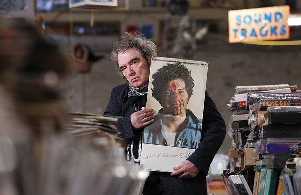 """Armand Schaubroeck, co-owner of the House of Guitars and a former rock artist, displays the album he cut in 1968, """"A Lot of People Would Like to See Armand Schaubroeck . . . DEAD."""" - PHOTO BY MAX SCHULTE"""