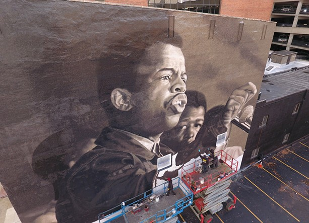 """Painters depict a young John Lewis in the mural """"I Am Speaking,"""" at 49 State St. in downtown Rochester. - PHOTO BY MAX SCHULTE / WXXI NEWS"""