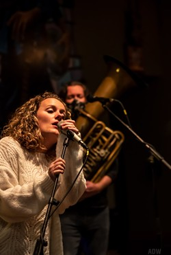 Teagan Ward (foreground) leads Teagan and the Tweeds in a live performance at Three Heads Brewing. - PHOTO BY AARON WINTERS