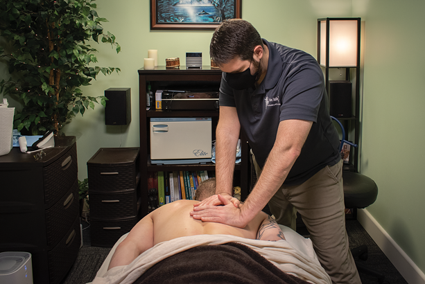 Shawn Belles of Pain Relief Massage & Wellness in Penfield works on a client. - PHOTO BY RYAN WILLIAMSON