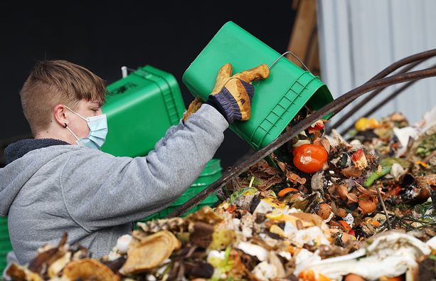 Beckett Putney empties household food scraps into a Dumpster at Impact Earth, a residential food scrap collector in Monroe County. - PHOTO BY MAX SCHULTE
