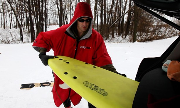 Aurelien Bouche Pillon suits up for a winter surf on Lake Ontario. - PHOTO BY MAX SCHULTE / WXXI NEWS