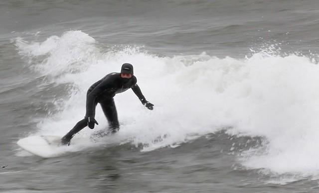 Aurelien Bouche Pillon surfs Lake Ontario in the dead of winter. - PHOTO BY MAX SCHULTE / WXXI NEWS