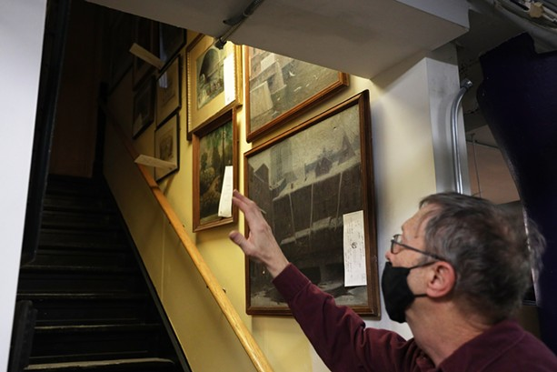 Rochester Historical Society archivist Bill Keeler found some wall space to hang paintings of Rochester in a stairway leading to the basement in the organization's new space. - PHOTO BY MAX SCHULTE