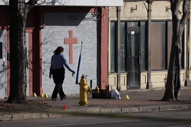 Rochester police examine an area outside of Open Door Mission where early Wednesday an officer shot a man who police said was brandishing a large knife. - PHOTO BY MAX SCHULTE