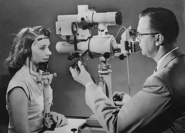Bausch + Lomb has deep innovation history in Rochester. Here, a doctor positions a patient before a B + L retinal camera, ca. 1953. Unidentified photographer. Gelatin silver print. - IMAGE COURTESY GEORGE EASTMAN MUSEUM