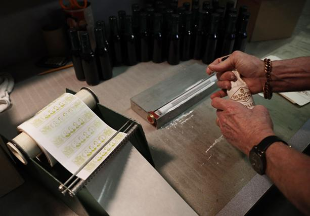 Just as in the olden days, all of Fee Brothers' bottles are labeled by hand. - PHOTO BY MAX SCHULTE