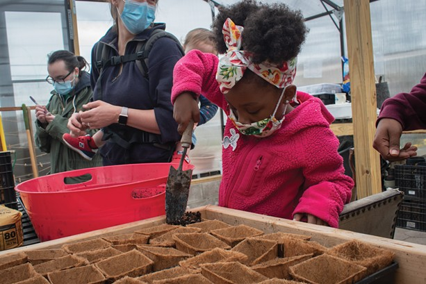 Myree helps her mother, Taproot Collective board chair Leslie Knox, plant some seeds in the greenhouse at First Market Farm. - PHOTO BY RYAN WILLIAMSON