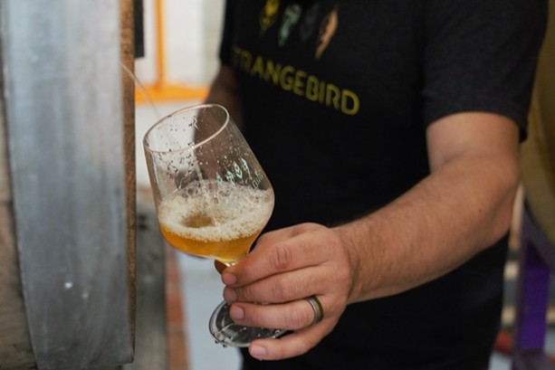Eric Salazar pours a glass of a Belgian Golden Ale straight from the barrel. - PHOTO BY GINO FANELLI