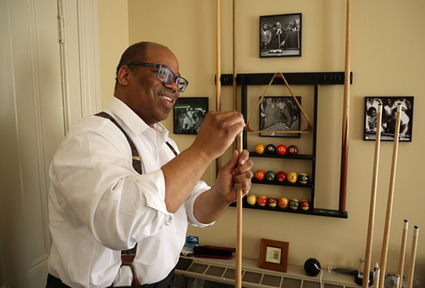 Van White chalks a pool cue as he prepares to break on the table that Martin Luther King Jr. played on as a student at Crozer Theological Seminary. White had the table restored and placed in his law office. - PHOTO BY MAX SCHULTE