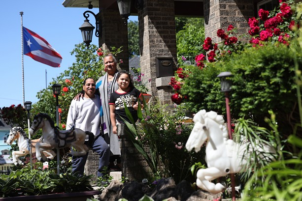 Carmen Rodriguez and Zenobio Rodriguez Jr.  with their granddaughter, Milani, at their home at the corner of North and St. Jacob streets, where they have decorated their yard with more than 120 toy horses. - PHOTO BY MAX SCHULTE