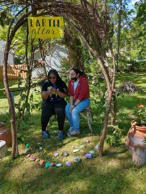 Youth educators Natasha Morrison and Alex Hubble sit at the Earth Altar they created outside of the Gandhi Institute in Rochester. - PHOTO PROVIDED
