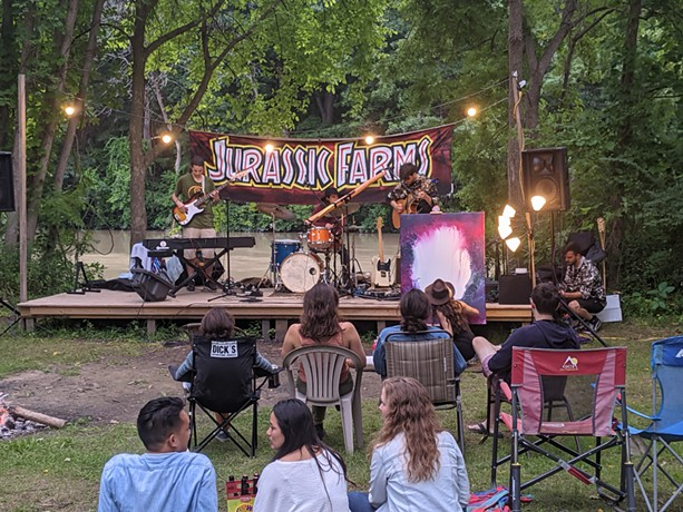 Pop-folk band Head to the Roots performs as Casey Arthur paints live in the foreground at Jurassic Farms. - PHOTO BY DANIEL J. KUSHNER