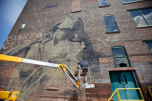 """South African artist Faith47 paints """"Rhapsody"""" on the Lofts at Michaels-Stern on Pleasant Street in 2012. - FILE PHOTO"""
