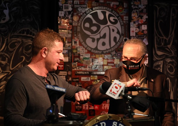 U.S. Senator Chuck Schumer and Bug Jar co-owner Aaron Gibalski hit each other's elbows during a March 31 press conference at the Bug Jar.  - PHOTO BY MAX SCHULTE / WXXI NEWS