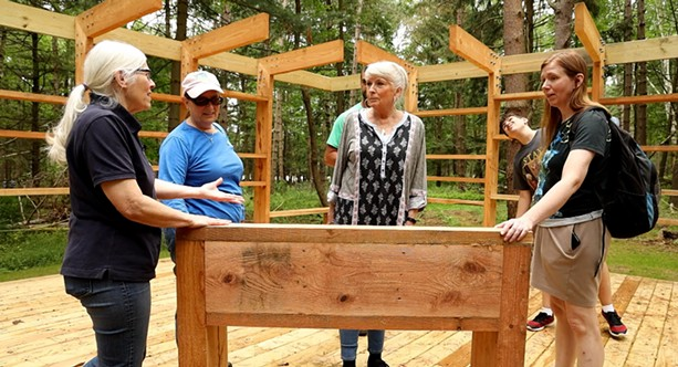 Loren Penman shows off a sensory table to Anne Quivey, Catherine Abida, Pat Strobel, Ali Abida and his mom, Catherine Abida at the Autism Nature Trail at Letchworth State Park. - PHOTO BY MAX SCHULTE
