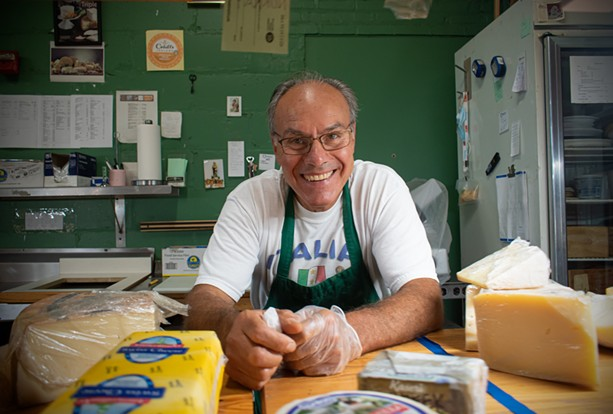 Vincenzo Giordano at the cheese counter of VM Giordano Imports Inc., which he opened in the Rochester Public Market nearly 30 years ago. - PHOTO BY JACOB WALSH