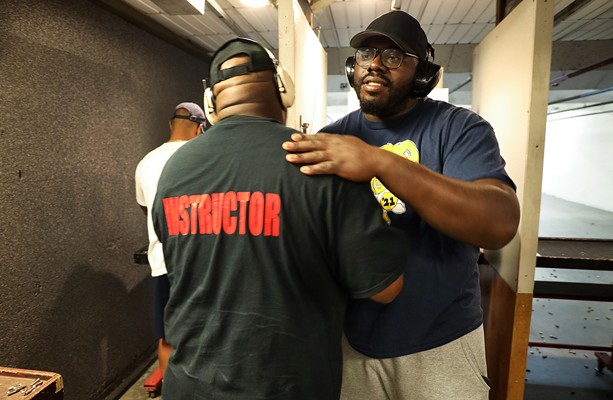 Ronnie Crawford gives a goodbye hug to Rochester African American Firearms Association Chief Instructor Mark Cochran. Crawford is an original member of RAAFA and owns a private security company. - PHOTO BY MAX SCHULTE