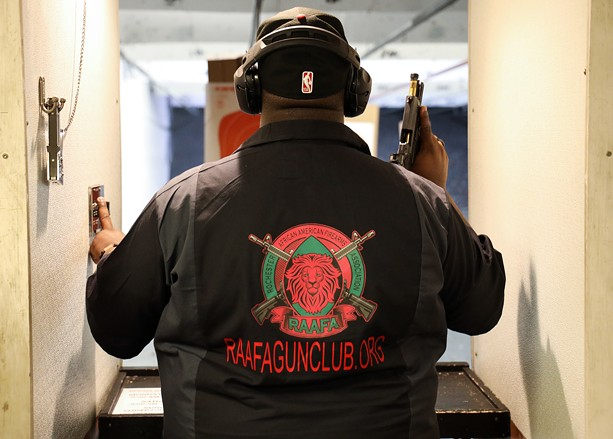 Paul Adell, a founder of the Rochester African American Firearms Association, sends a paper target down range before practice at The Firing Pin in Bergen. - PHOTO BY MAX SCHULTE