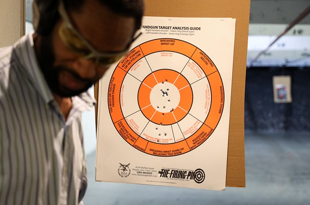 Quinn Lawrence, one of the self defense instructors with the Rochester African American Firearms Association, checks his target after shooting a pistol during practice at The Firing Pin. - PHOTO BY MAX SCHULTE