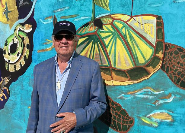 """Artist Peter Jemison stands in front of his """"Water is Life"""" mural, which was installed on the Floreano Convention Center facing the Genesee River. - PHOTO BY REBECCA RAFFERTY"""