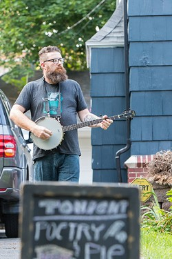 Jacob Rakovan strums the banjo outside of the July 11 Poetry & Pie Night. - PHOTO BY JOHN SCHLIA