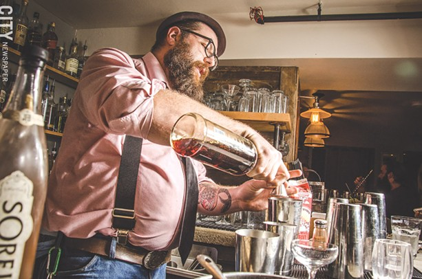 """Bartender Jacob Rakovan mixes the """"Cratchit's Comfort"""" at The Daily Refresher. - PHOTO BY MARK CHAMBERLIN"""