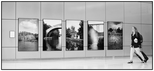 Installation view of Richard Margolis' photographs at the Greater Rochester International Airport. The images have been removed and advertisements have been installed in their place. - PHOTOGRAPH COURTESY OF RICHARD MARGOLIS