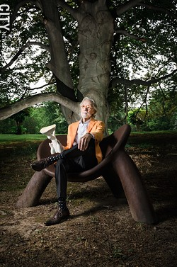 Wendell Castle, photographed outside his Scottsville studio in 2016, seated on a chair of his own creation and holding a scale model of another sculpture. - FILE PHOTO