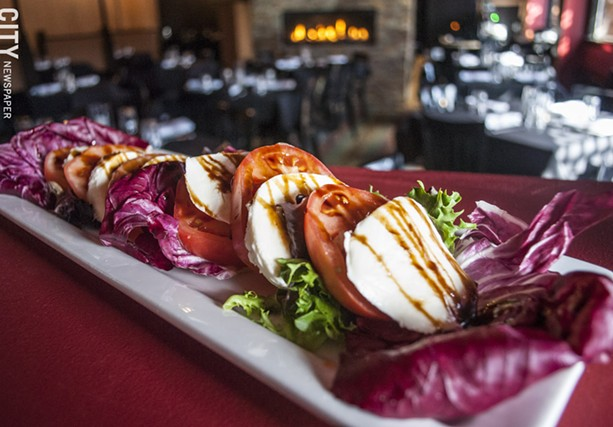 Heirloom Tomato Salad with fresh mozzarella, spring lettuces, radicchio, and a garlic-balsamic reduction. - PHOTO BY RENÉE HEININGER