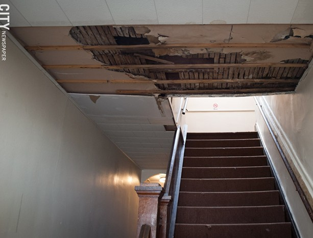 A ceiling falling apart in the the 967 Chili Avenue apartment building entrance way. - PHOTO BY JAKE CLAPP