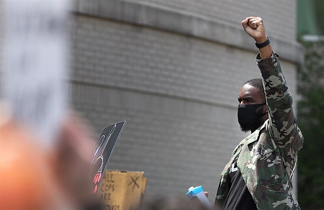 An unidentified man stands with a clenched fist at the Black Lives Matter, Stop Killing Us! rally in Rochester on May 30, 2020.