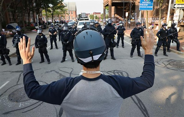 A protester faces off with a line of police at City Hall on  Sept. 16, 2020.